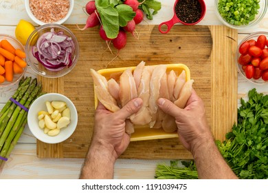 Chef preparing chicken strips with vegetables and seasonings on cutting board for dinner perhaps lunch