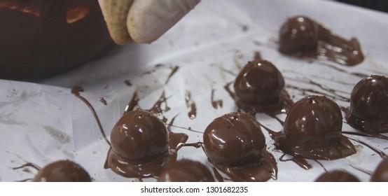 Chef preparing chocolate sugarplum with a pinch. Fingers in close up.
