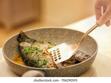 Chef preparing delicious fishes on frying pan