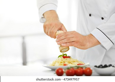 Chef preparing delicious pasta in kitchen