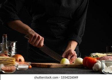 Chef, chef preparing a dish, chopping onions. Salad. Delicious and healthy food. Black background. Cooking method. Cooking, gastronomy, restaurant service.
