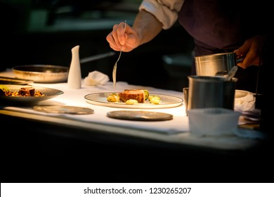 Chef preparing a dish with meat on a plate under a light. The chef is meticulous.