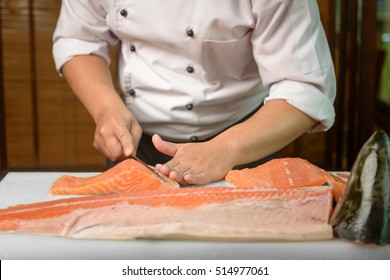 Chef preparing a fresh salmon on a cutting board, Japanese chef in restaurant slicing raw fish for salmon sushi, ingredient for seafood dish.