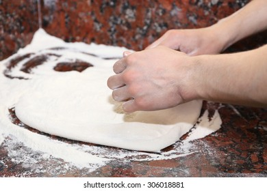 Chef preparing pizza dough on marble table, closeup