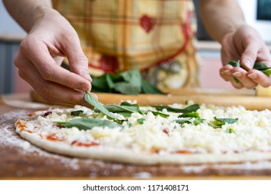 Chef preparing pizza on marble table, closeup