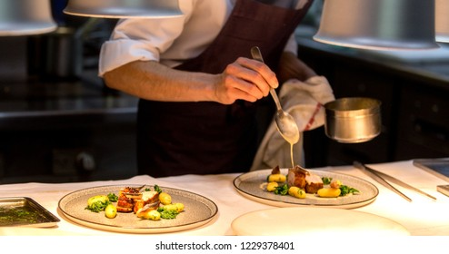 Chef preparing a plate made of meat and vegetables. The chef is pouring sauce on two plates.