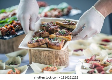 Chef preparing raw beef tartar mini breads on a catering event.