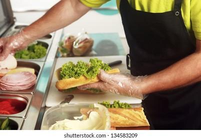 A chef preparing a sandwich with fresh salad