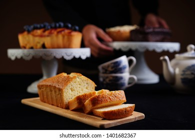 A chef preparing a table full of loaf cake desserts. Vanilla loaf cake slices on a brown cutting board with blueberry loaf cake on cake stand at the back. Selective focusing. Dark food photography.