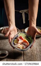 chef presenting salmon poke avocado seaweed-pickled carrots