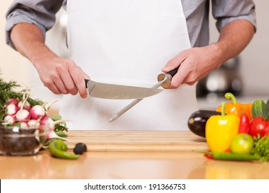 Chef. Professional chef sharpening knife inlcluding assorted fresh vegetables