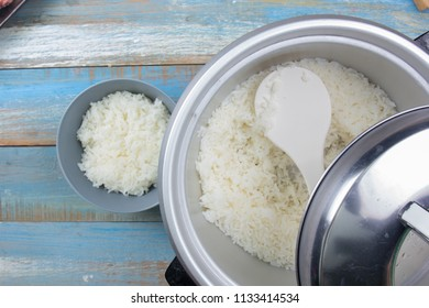 Chef put cooked rice with plastic ladle to cup in electric rice cooker