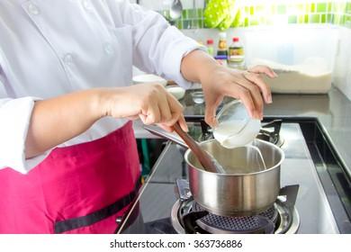 Chef put the milk for preparing food in pot