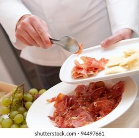 Chef puts jamon on a plate. Serrano, jamon.