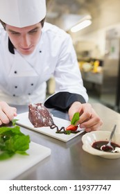 Chef putting mint on the dessert plate with cake in the kitchen