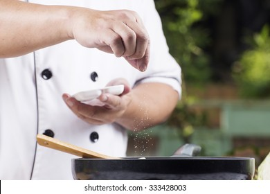 Chef putting Salt to the pan for cooking vegetable