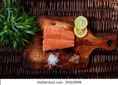 Chef ready to pickle fresh salmon steak. A small piece of salmon is on the board for cutting meat and fish is scattered next to the salt and pepper