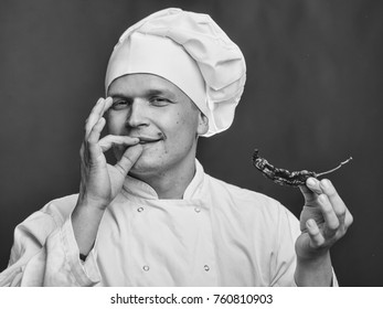 chef with a red chili pepper in his hands in white uniform and hat on purple background with okey gesture