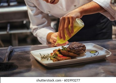 Chef In Restaurant Arrangin And Decorating Food
