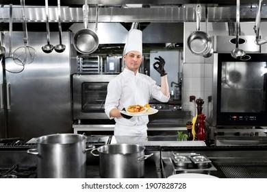 """Der Chefkoch im Restaurant hält einen Teller mit Fertiggerichten bereit und zeigt das Zeichen """"OK"""""""