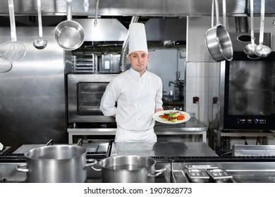 Koch in einem Restaurant hält einen Teller mit einem Fertiggericht
