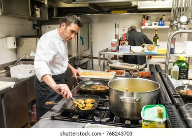 Chef in a restaurant kitchen cooking meat and mushrooms. Adult cook at work, wearing white uniform and black apron, focused on cooking.
