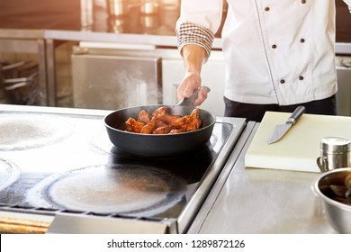 Chef roasting chicken pieces on stove. Chicken wings cooking in restaurant kitchen.