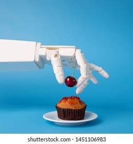 Chef robotic assistant in kitchen technology. Robot hand decorating sweet cupcake with fresh cherry, blue background