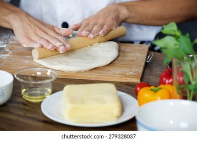 Chef roll out the dough for home made pizza