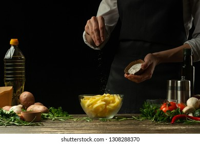 Chef salting french fries on a background with vegetables. Cooking tasty but harmful food