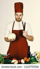 Chef with serious face holds cabbage and knife on white background. Cook works in kitchen near vegetables and tools. Cuisine and cooking concept. Man in burgundy hat and apron holds ingredient