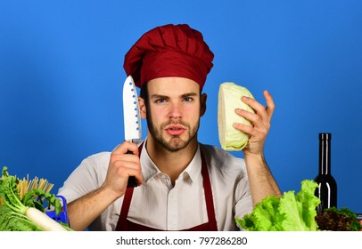 Chef with serious face holds cabbage and knife on blue background. Man in cook hat and apron ready to cut cabbage. Cook works in kitchen with vegetables and tools. Kitchenware and cooking concept.