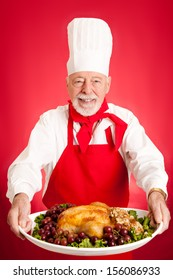 Chef serves beautiful stuffed turkey garnished with grapes.  Could also be a large chicken.