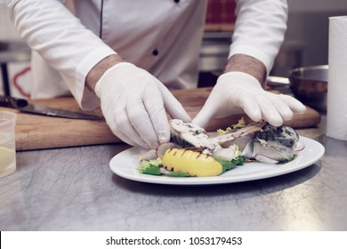 Chef is serving steamed mackerel fish, healthy dish, toned