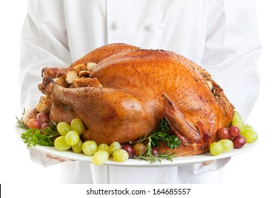 Chef serving a stuffed turkey garnished with grapes.
