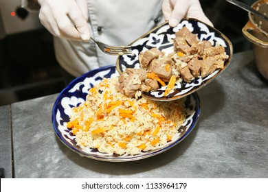 Chef is serving traditional Middle Eastern pilaf in restaurant kitchen