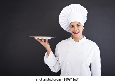 Chef showing empty plate. Happy smiling portrait of female in chef uniform and chef hat isolated on dark background.