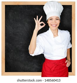 Chef showing menu blackboard and Perfect hand sign. Woman in front of blank menu blackboard. Happy female chef, cook or baker by empty chalkboard menu display wearing chef whites uniform and hat