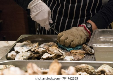 A chef is shucking an oyster