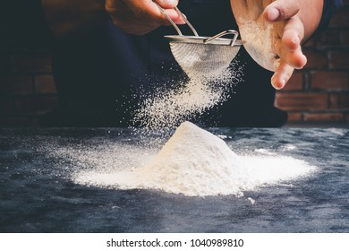 Chef sifting flour on black table