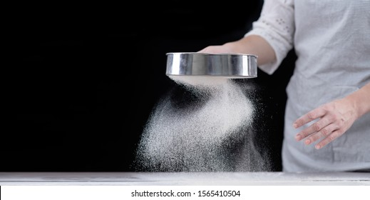 Chef sifts flour through a sieve on a wooden table. Empty space for text. Isolated on dark background
