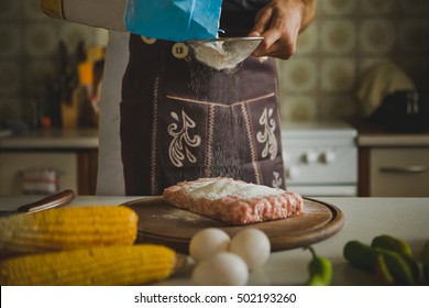 chef sifts the flour. young man cook breaks egg. processes in the kitchen cooking.