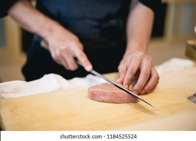 chef slices fresh fish fillet at sushi bar