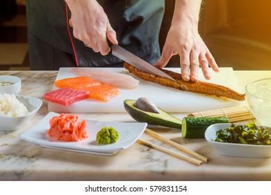 Chef slicing eel on a cutting board. Fish fillets, rice, sesame seeds, wasabi, gari, chopsticks, an avocado, a cucumber and a bamboo mat. Making professional sushi.