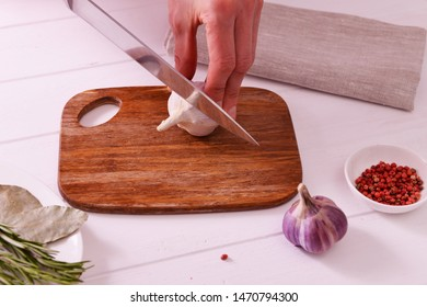 Chef slicing garlic on the cutting board with a knife,  on a white wooden background. Raw garlic and spices on wooden table.