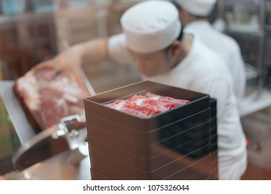 A chef is slicing a raw beef by meat slicer for shabu shabu in the japanese restaurant.