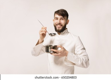 Chef smelling aroma from saucepan. Aroma of a dish. Head chef smelling the food standing against white background. Chef smelling the aroma of a dish.