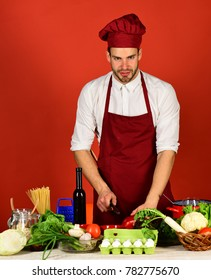 Chef with smiling face holds knife and red bell pepper on red background. Man in cook hat and apron chops pepper. Food preparation concept. Cook works in kitchen near table with vegetables and tools.