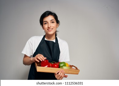 chef smiling holding vegetables on a cooking tray