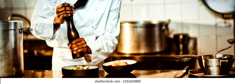 Chef sprinkling pepper on a meal in commercial kitchen